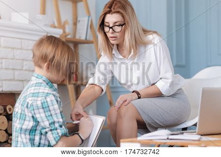 Repeat after me. Serious young woman sitting opposite her patient helping him with task while holding her hand on her knee