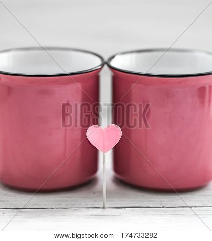 beautiful pink Cup with heart on a stick on a light wooden background, concept drinks