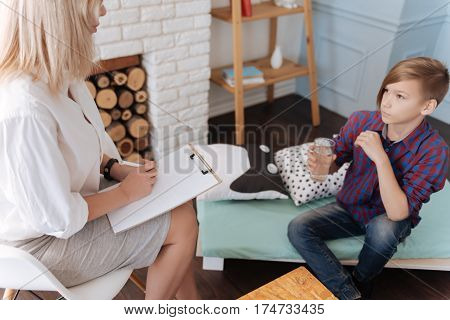 Would you like to drink. Serious male person sitting on the sofa holding his elbow on his leg looking on psychologist