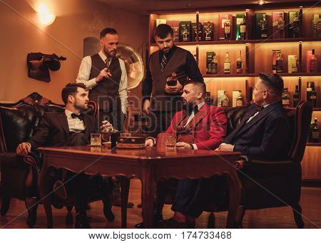 Group of confident men speaking in gentlemen's club