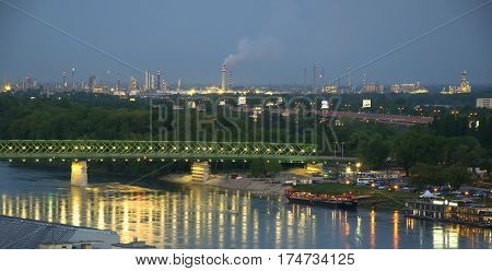 Bratislava industrial zone behind Danube river bridge and river ships at twilight view from casrle hill Slovakia