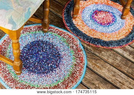 Two handmade colorful rugs on a wooden floor with a pair of chairs