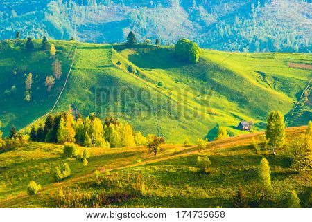 Carpathian's village hills in a warm sunset light covered with fresh spring grass. Lonely wooden house in a valley