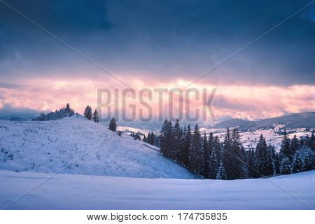 Bright colorful winter sunset in a snow-capped Carpathian mountain valley. Ukraine Europe
