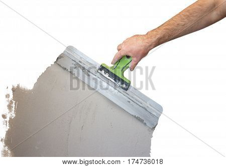Man's Hand With Spatula In The Repair Room. Plasterer Worker Aligns Wall Plaster Or Lime. Isolated O