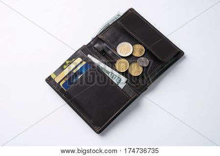 Open brown leather wallet with dollar cash coins debit credit cards isolated on white background