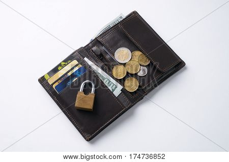 Open brown leather wallet with dollar cash coins debit credit cards inside and locked pad lock.Business safety and finance protection concept