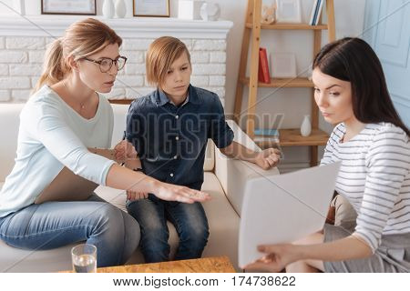 Just look on it. Very attentive boy wearing jeans costume holding left hand on back of sofa while looking straight on paper