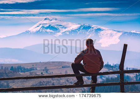 A hiker sitting on a wooden fence and enjoy mountain valley with snow-capped peak on a skynine