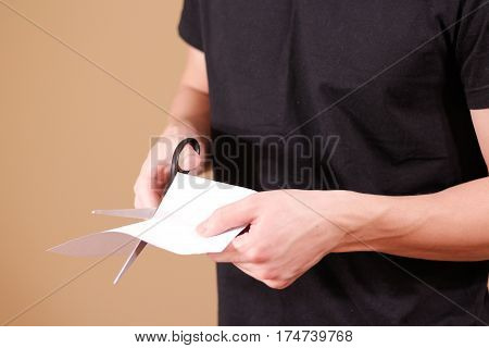 Man Hand Cut White Paper With Scissors.