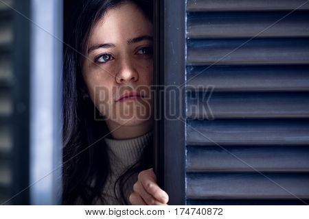 Crying Woman Watching Outside from a Wooden Window Shutter