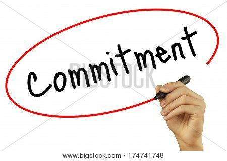 Man Hand writing Commitment with black marker on visual screen. Isolated on background. Business technology internet concept. Stock Photo poster
