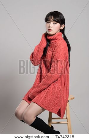Studio portraits of twenties Asian women staring at camera sitting in chair