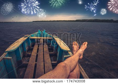 Men siting in a old rustic boat on a river and enjoy holiday firework at the night sky