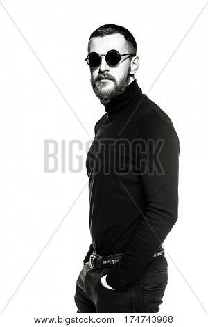 Black-and-white portrait of a handsome bearded hipster man wearing round sunglasses. Male fashion. Isolated over white.