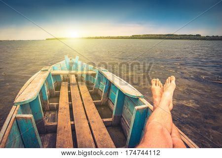 Men on weekend siting in a old rustic boat on a river and enjoy sunrise