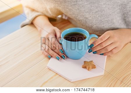 Close up of arms of young girl is sitting near table. She touching to blue cup of invigorating coffee