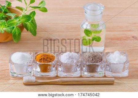 alternative natural mouthwash with mint toothpaste xylitol or soda turmeric - curcuma himalayan salt clay or ash coconut oil and wood toothbrush on wooden background