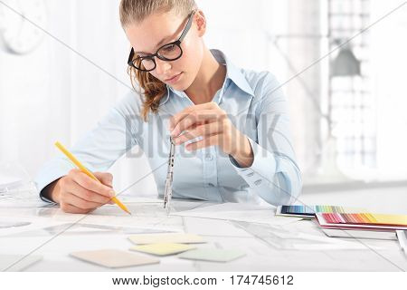 interior designer draws at desk in office with pencil and compass Planning Concept