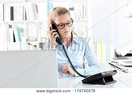 woman talking on phone in office at desk in front of computer