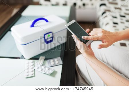 Woman using smartphone for buying drugs in internet pharmacy and getting online medical consultation with doctor at home. White box with first aid kit and pills in blister packs on table.