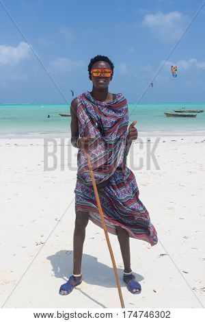 Traditonaly dressed black man with funny sunglasses on Paje beach. Maasai warrior on picture perfect tropical sandy beach on Zanzibar, Tanzania, East Africa.