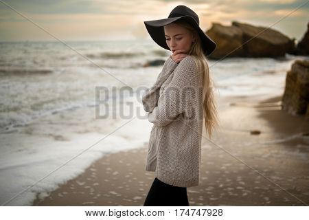 Woman In Hat And Sweater On Winter Beach At Sunset.