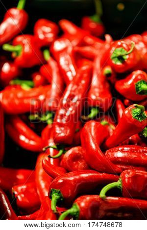 lot of red chilli peppers in market stall, background.