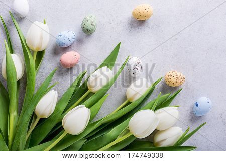 Beautiful white tulips with colorful quail eegs on light gray stone background. Spring and Easter holiday concept with copy space.