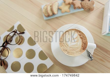 Close up of Small cup with coffee on white round utensil near closed notebook. Cookies are beside mug of nonalcoholic beverage. Top view