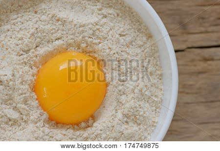 Flour and egg ready for mixing on wooden table