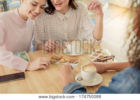 Hilarious pretty young women are sitting near table. Female person is taking small cookie from rectangular stand