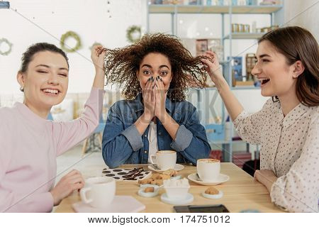 Hilarious young women are sitting in light room of cafe. They merrily laughing while touching curly hair of mulatto girl