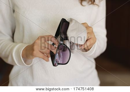 Women Hand Cleaning Black Sunglasses Lens With Blur Brown Background.