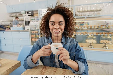 Portrait of Hilarious girl is sitting near table. She holding white cup of coffee and looking at camera