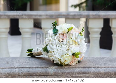 Beautiful wedding bouquet of eustoma and roses on vintage marble banister