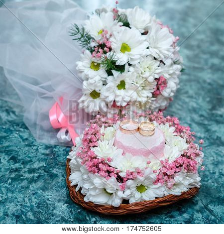 Two gold wedding rings on Beautiful white and pink bouquet in rustic basketry.. Close up.