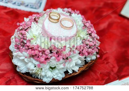 Two gold wedding rings on Beautiful white and pink bouquet in rustic basketry. Red fabric background. Close up.