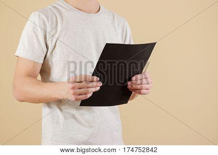 Man Holding Black A4 Paper. Read Booklet. Leaflet Presentation. Pamphlet Hold Hands. Man Show Clear