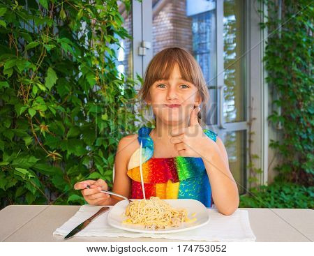 Little girl at lunch in cafe eating delicious pasta and happy meal