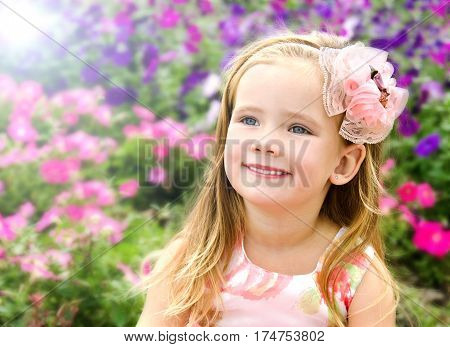 Portrait of cute little girl near the flowers in summer day outdoor