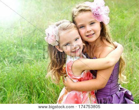 Portrait of two embracing adorable little girls in princess dresses outdoor