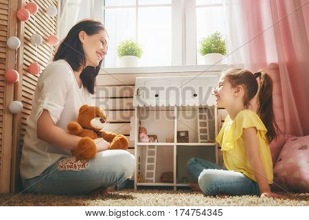Happy mother and daughter girl play with doll house at home. Funny lovely family are having fun in kids room.