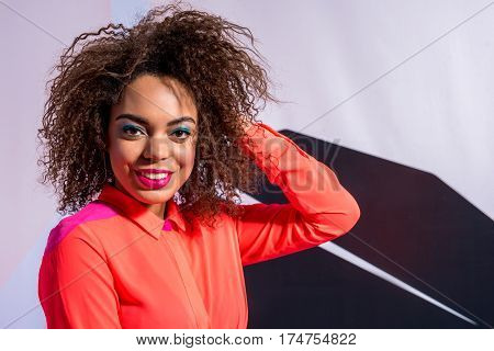 Waist up portrait of Attractive mulatto face of beaming young woman with blue face-painting is on background of colorful wall