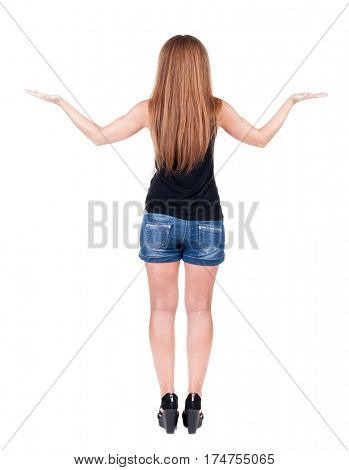 back view of surprised beautiful  young redhead woman with hands up. Girl in blue shotrs. Rear view people collection.  backside view of person.  Isolated over white background.