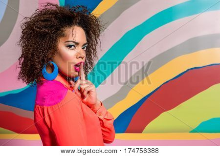 Hush, do not tell anyone. Outgoing woman showing by gesture keeping calm while situating near painting poster. Copy space