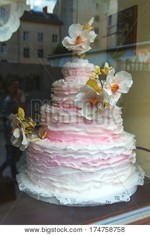 pink and white 4-tiered wedding cake with flowers. wedding trend creamy dessert.