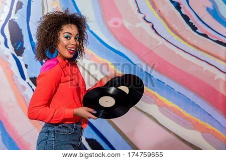 Portrait of Cheerful female with bright makeup keeping gramophone records in hands while locating opposite colorful wall. Copy space