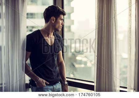 Sexy handsome young man standing next to window curtains, looking out