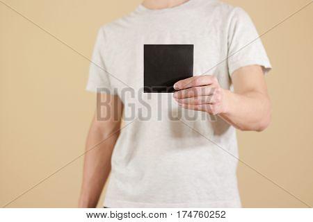 Man Showing Blank Black Square Flyer Brochure Booklet. Leaflet Presentation. Pamphlet Hold Hands. Ma